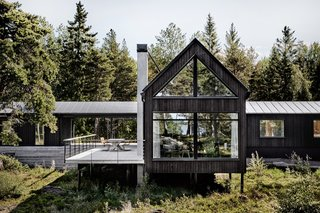 The house is clad in vertical planks of black-painted fir.