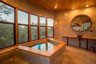 The custom concrete soaking tub is set in front of a wall of windows.