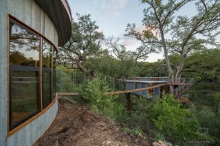A 60-foot-long suspension bridge links the treehouse with the detached bathhouse.
