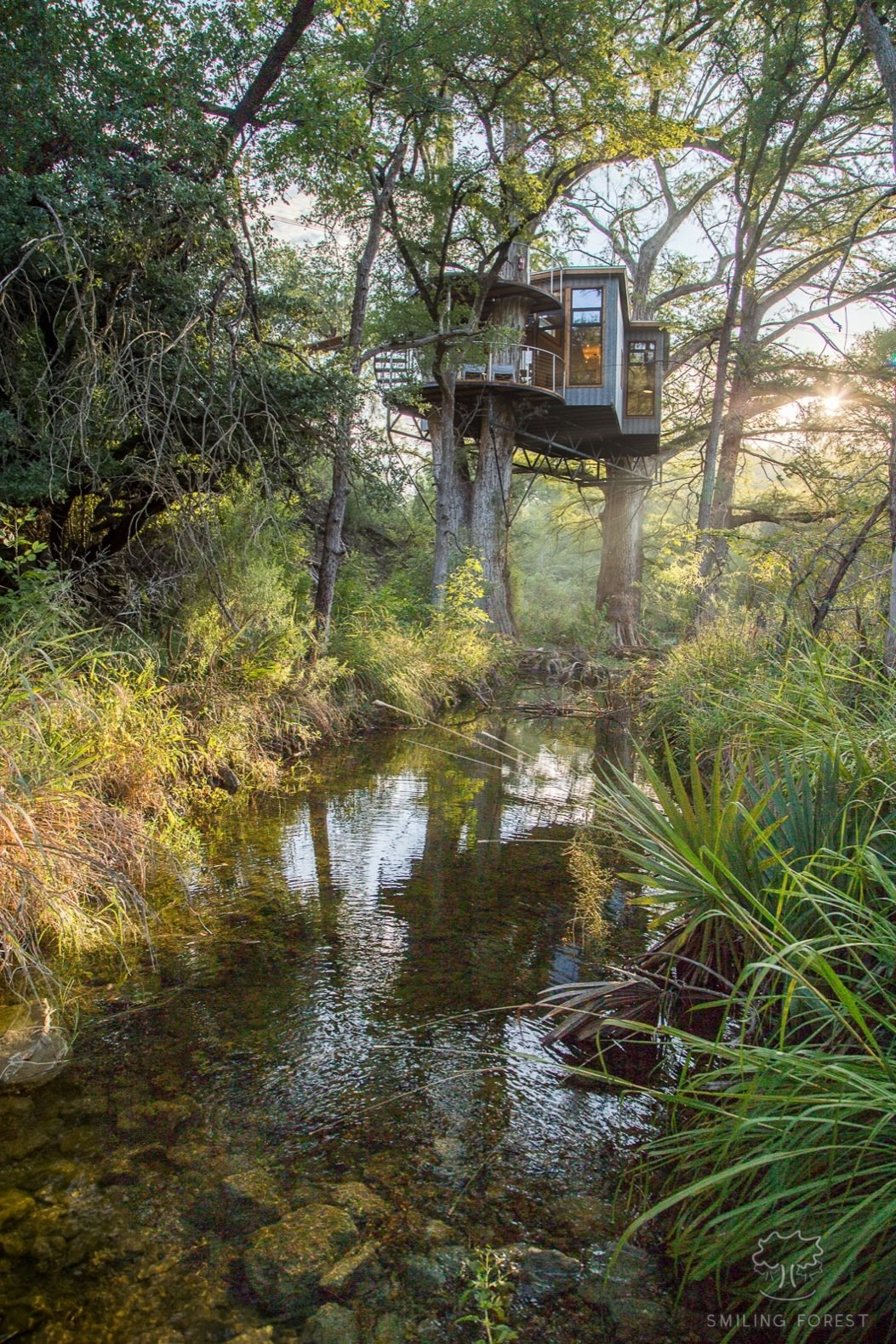 "Exterior, Metal Roof Material, Treehouse Building Type, Flat RoofLine, and Metal Siding Material Elevated above a spring-fed creek, Yoki draws inspiration from the ""healing powers of water.""  Photo 2 of 15 in Escape to the Texan Treetops in This Eco-Luxe Treehouse"