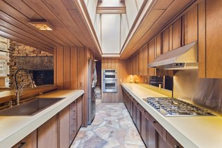 Illuminated by a newly installed skylight, the kitchen has all new stainless kitchen appliances.