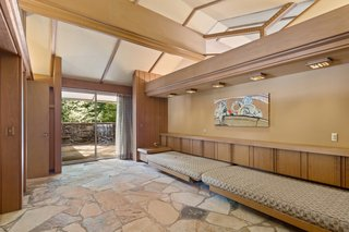 Sliding glass doors connect to a patio, which has new flagstone and a waterfall fountain.