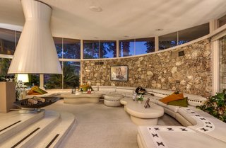 Anchored by a circular fireplace and sculptural hood, the circular living room features a 40-foot-long built-in seating area, as well as walls of glass.