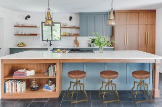 The custom shaker style cabinets were painted Benjamin Moore Knoxville Gray and mixed with walnut cabinets with an island overhang by Elite Remodeling Concepts, LLC. The stools are from Dovetail Furniture.