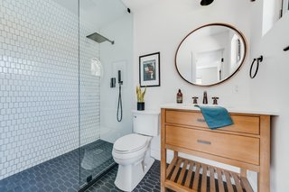 The guest bath pairs black limestone picket floors from Floor and Décor with white porcelain picket from Floor and Décor for the shower walls. The vanity is by Sage Hill Designs, and the round mirror is from Hayneedle.