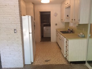 """Before: """"We removed the old walled-off kitchen in the corner, created a pantry in its place, and expanded the kitchen from front to back of house with a new floating kitchen island,"""" Janie notes."""