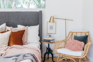 A corner of the master bedroom is furnished with a Serena Lily side chair, a Target floor lamp, and a Home Goods side table.