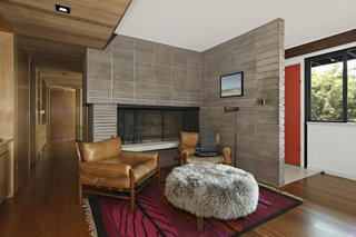 Behind the bright red entrance door is a concrete block fireplace and a snug den.