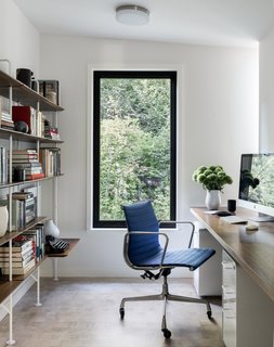 The office, located adjacent the master bedroom, is smartly outfitted with a vintage Aluminum Group Management chair by Herman Miller, a custom walnut plywood desk by Kerf Design, and Hitch bookcases from Blu Dot.