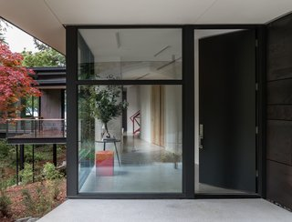 An oversized entrance door leads to an angled hallway that obscures views to create an element of surprise. The Vollen bench in Custom Red Lacquer is from Chadhaus.