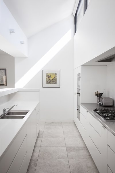 The white kitchen is equipped with NEFF appliances as well as Caesarstone Snow and stainless-steel countertops.