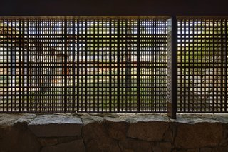 The lath screen offers a glimpse of the grassy hill from the entryway.