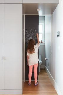 A hidden powder room is concealed behind the kitchen unit's sliding chalkboard door.