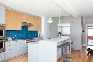 The light-filled kitchen features Leo Bar stools from Room and Board, Doo-Wop pendant lights by Louis Poulsen, and GE Monogram appliances. The backsplash is Heath Tile and the countertops are Solid Surface.
