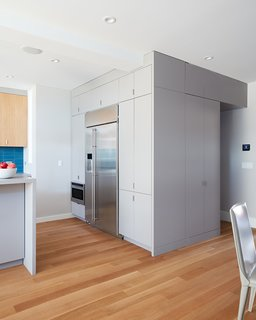 """The kitchen also contains a custom casework """"cube"""" that conceals appliances and a hidden powder room."""