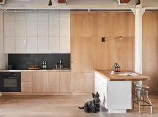 """""""Since the kitchen is open to the space, we tried to make it look as clean as possible with slab-faced cabinets flush to the walls, simple tile, and clean appliances,"""" Shively says. The island is inspired by Alvar Alto's designs."""