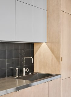 A backsplash featuring custom matte black ceramic tiles by Waterworks is paired with stainless steel countertops. The timber cabinets, by JRs Custom Cabinets, are made of white oak.