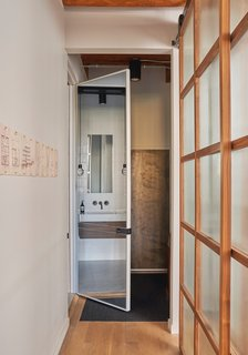 A full-length mirror on one side of the 10-foot-tall door brings additional light into the bathroom.
