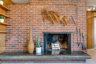A masonry core at the heart of the home features a cantilevered, polished concrete hearth that has naturally darkened with age.