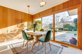 Floor-to-ceiling windows pull views of the backyard patio into the dining area.