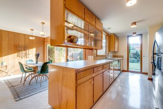 The kitchen is outfitted with birch cabinetry and a pull-out breakfast bar.