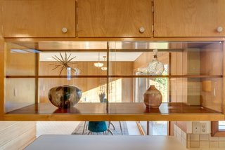 Open shelving creates flow between the kitchen and dining room.