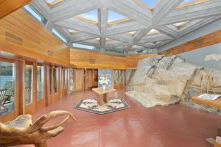 """The naturally occurring """"whale rock"""", a key part of Wright's sketches, cuts into the dramatic entry hall that's bathed in natural light. The massive rock measures 12 feet in height and 60 feet in length."""