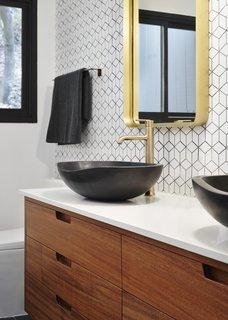 The renovation introduced new plumbing fixtures, lighting, custom wood vanities, and tiled walls in the bathroom.