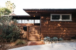 The midcentury home is clad in horizontal planks of redwood.