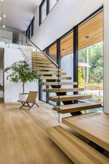 The sculptural stairway is fitted with white oak floating treads, a steel stringer, and a glass guardrail.