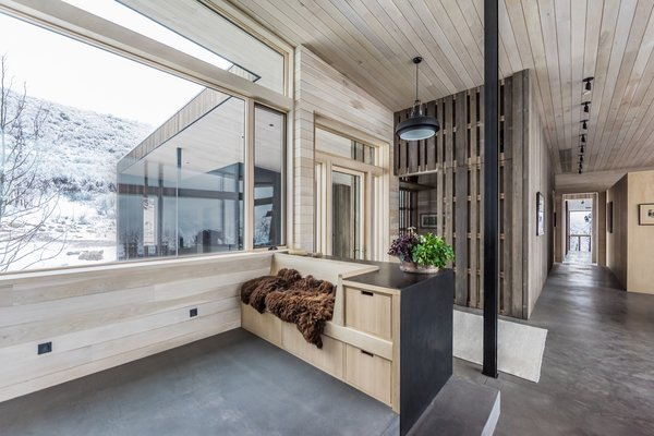 The exposed concrete floors, also equipped with radiant heating, help passively cool and heat the home in summer and winter, respectively. The bridge leading to the guest wing can be seen to the right of the mudroom.