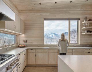 The oversized kitchen window frames spectacular views of Snowmass. Matching the white oak palette are pale Caesarstone countertops.