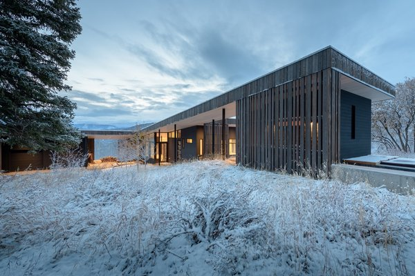 The angled roof mimics the sloped terrain and connects the cedar-lined sauna (on the right) to the main house and garage.