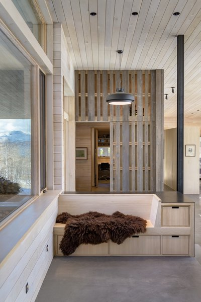 At the entry, a glimpse of the mudroom with the vertical-slat sliding door open.