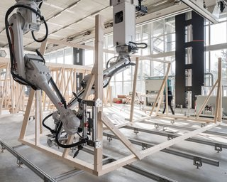 Robots cut, hold, and position the timber elements.