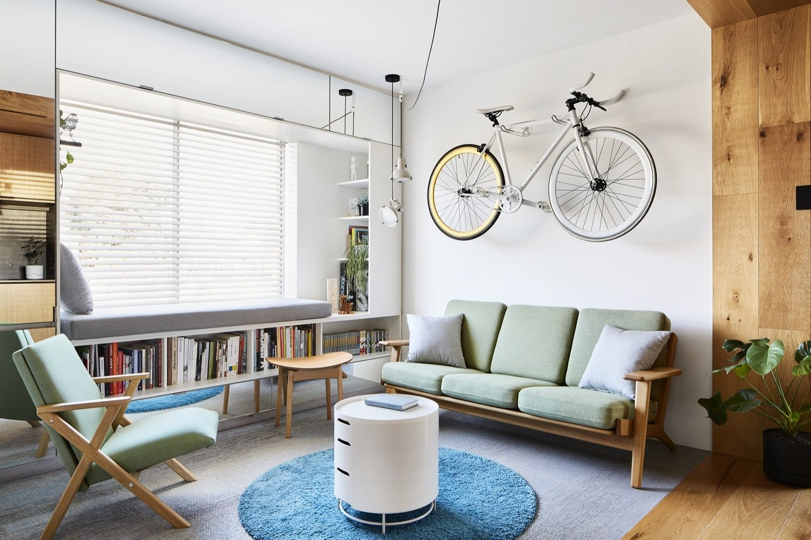 The fixed-gear bicycle hanging above the couch serves as an art piece; Chen no longer rides the bike. Le Corbusier Projecteur 165 pendant lights hang in the corner.