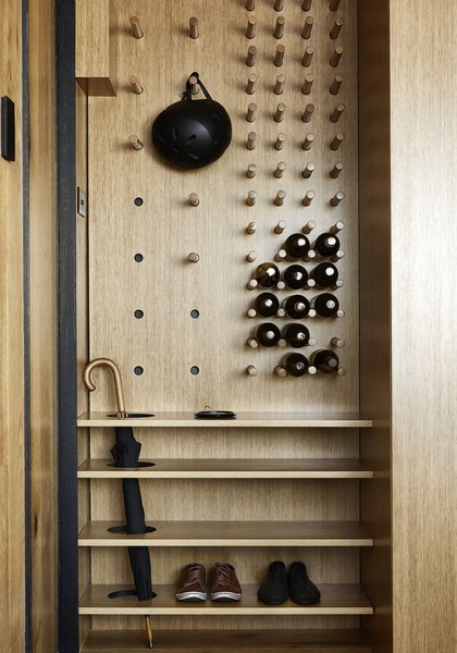 The multifunctional organizer at the entry includes an umbrella stand, a shoe rack, and an adjustable pegboard that serves as a wine rack and hat/helmet rack.