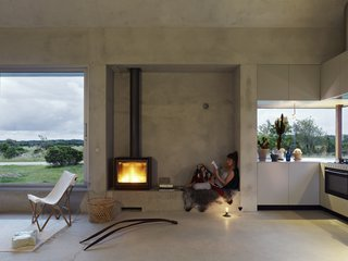 To minimize the home's energy footprint, the floor and foundation are made from cast concrete. Large openings allow for natural ventilation, while surrounding trees help create a cool microclimate. The house is powered by geothermal energy.