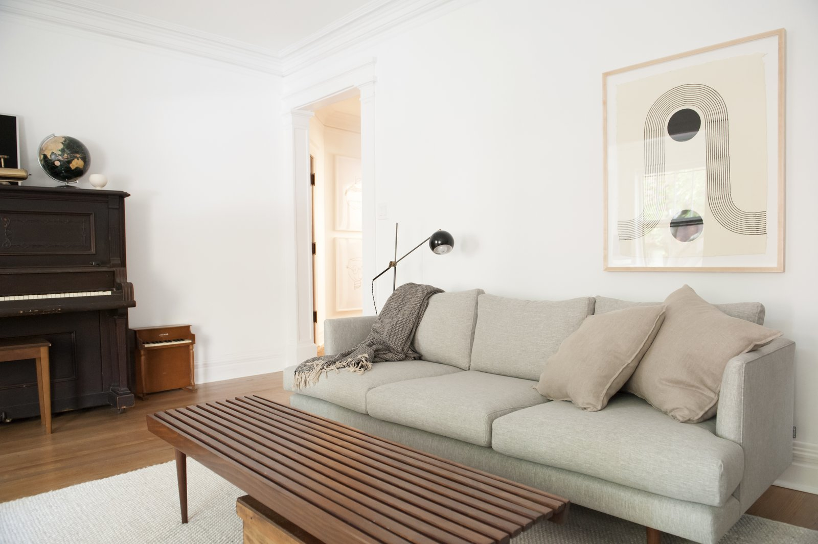 Living Room, Sofa, Coffee Tables, Floor Lighting, Medium Hardwood Floor, and Rug Floor  Best Photos from Simple and Beautiful Chicago Family Apartment