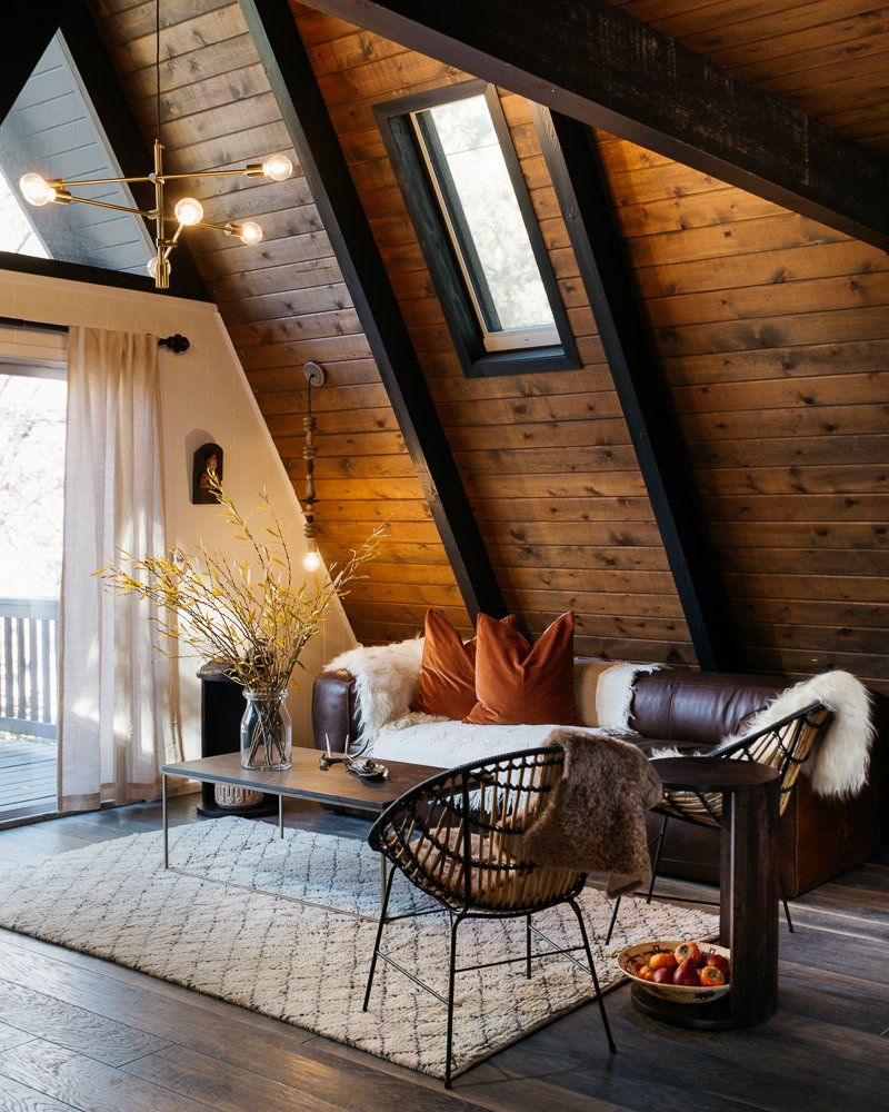 Living Room, Sofa, Chair, Coffee Tables, End Tables, Ceiling Lighting, Pendant Lighting, and Dark Hardwood Floor  Best Photos from Big Bear A-Frame Receives Boho Eclectic Transformation