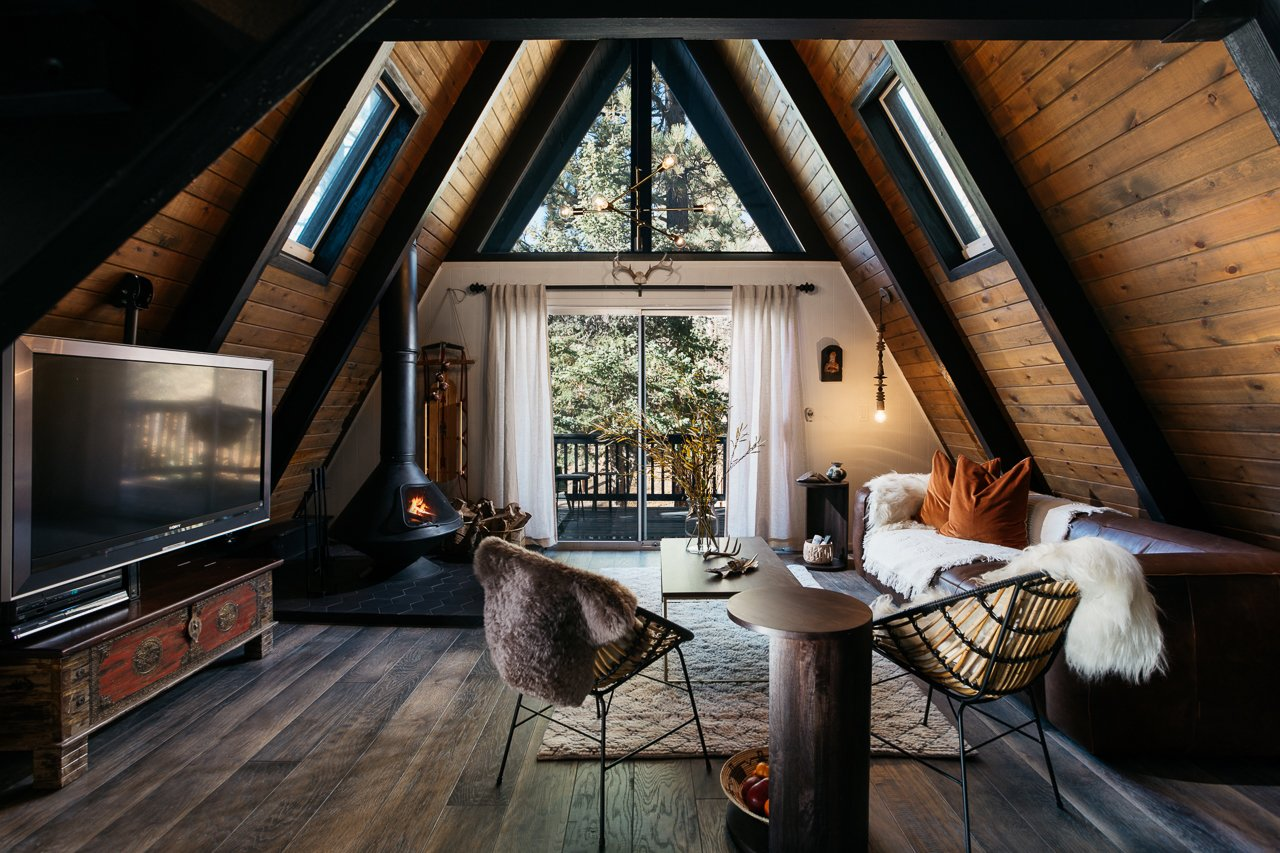 Living Room, Chair, Sofa, Coffee Tables, End Tables, Ceiling Lighting, Pendant Lighting, Dark Hardwood Floor, and Wood Burning Fireplace  Big Bear A-Frame Receives Boho Eclectic Transformation