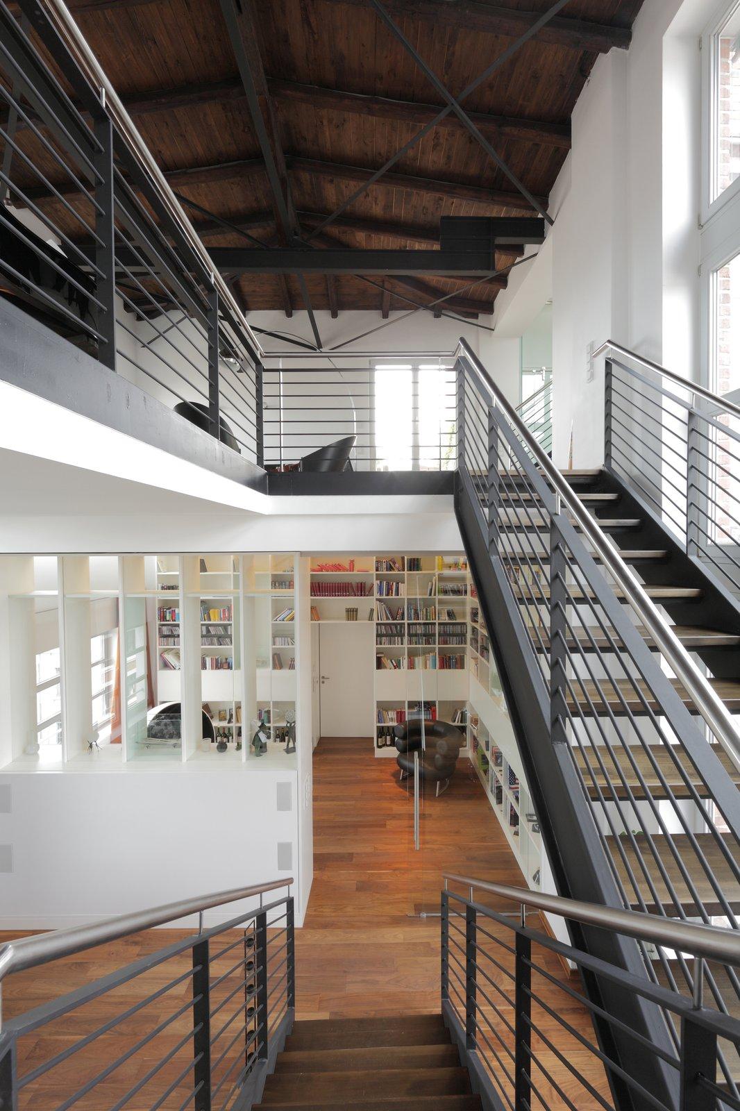 Living Room, Bookcase, Media Cabinet, Desk, Ottomans, Sofa, Lamps, Ceiling Lighting, and Medium Hardwood Floor  Penthouse Apartment in Bielefeld