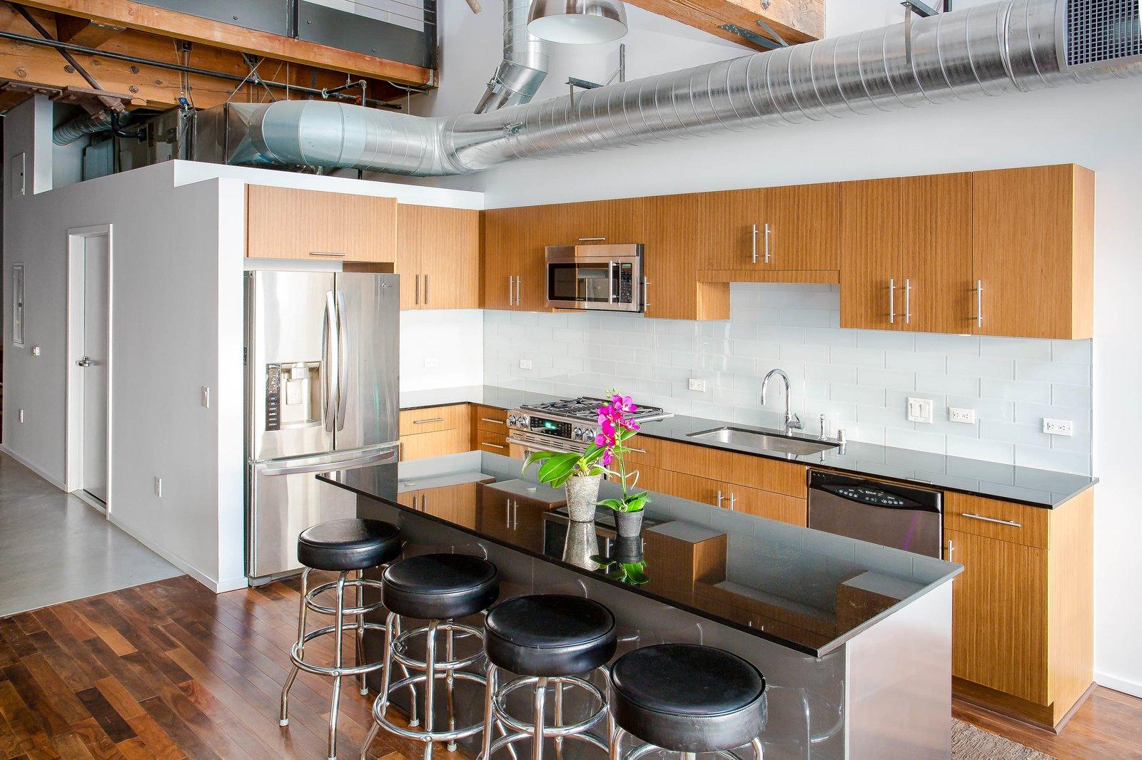 Kitchen, Refrigerator, Microwave, Dishwasher, Wood, Medium Hardwood, Subway Tile, Ceiling, Pendant, Granite, and Drop In  Best Kitchen Dishwasher Subway Tile Photos from Modern Downtown LA Loft
