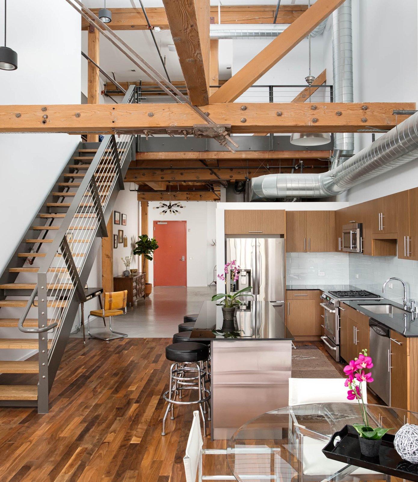 Kitchen, Granite Counter, Wood Cabinet, Ceiling Lighting, Pendant Lighting, Drop In Sink, Medium Hardwood Floor, and Subway Tile Backsplashe  Best Photos from Modern Downtown LA Loft