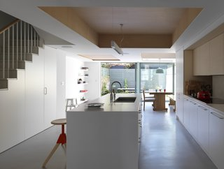 At this home renovation in England, the architects kept the interiors minimal and stripped back, allowing for extra space to be used by the family as they pleased. A kitchen island with exposed plywood on the interior but painted on the exterior doubles up as a breakfast bar, and holds storage space for three Magis swivel beech barstools to be tucked away when not in use.