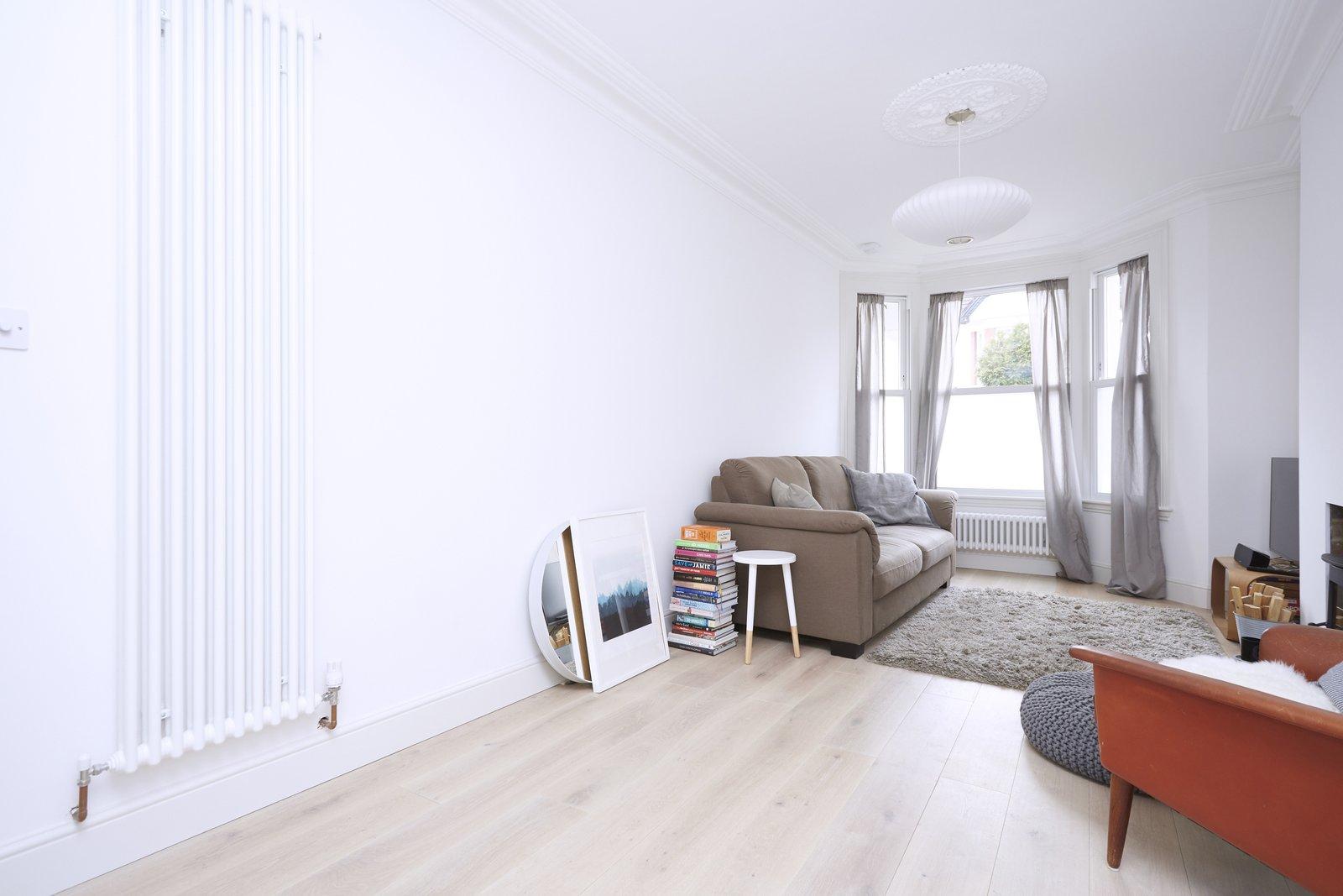 Living Room, Sofa, Coffee Tables, Chair, Ceiling Lighting, Medium Hardwood Floor, Light Hardwood Floor, and Wood Burning Fireplace  SW House by Studio AVC