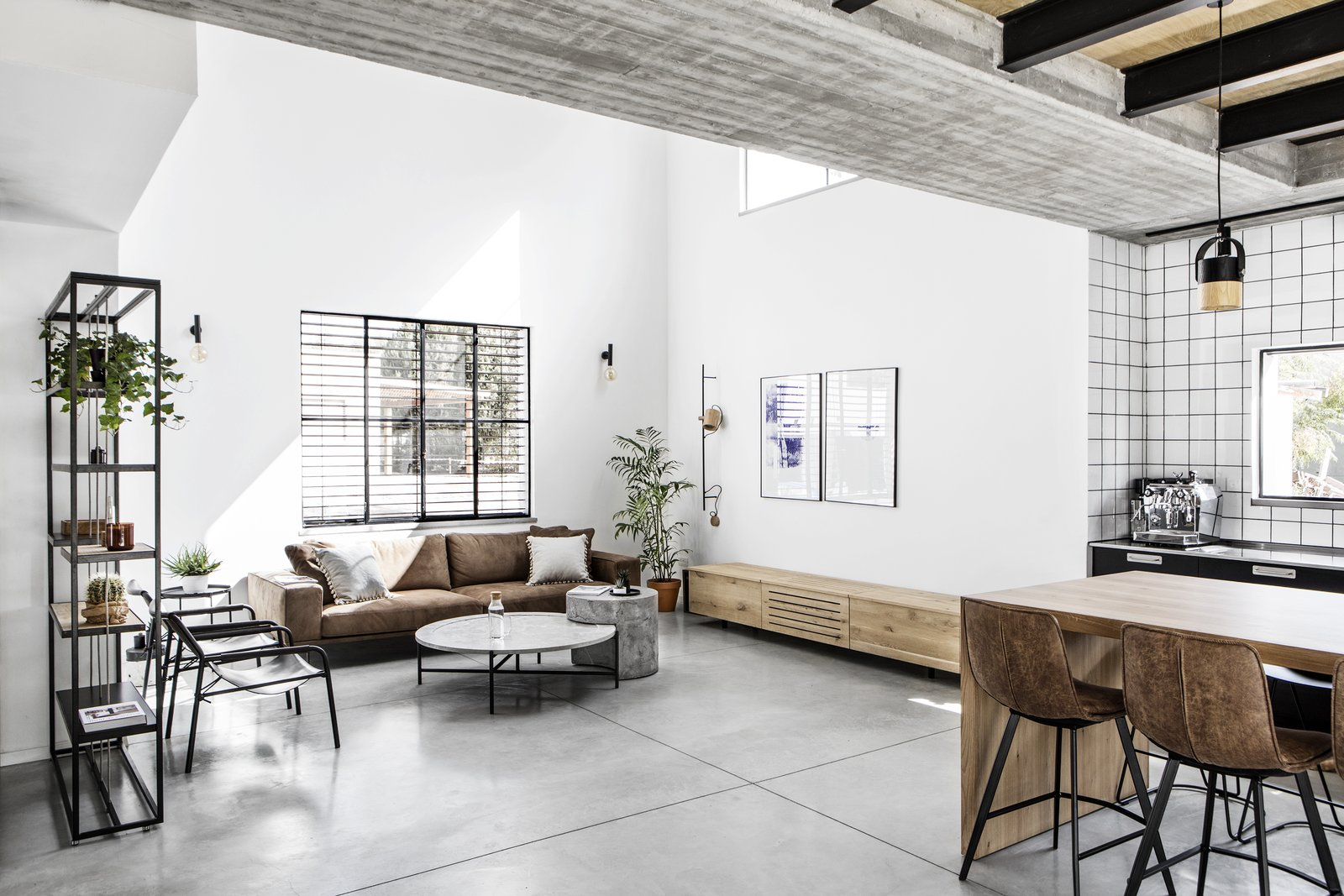 Living Room, Sofa, Ottomans, Chair, Coffee Tables, Console Tables, Bookcase, Pendant Lighting, Wall Lighting, and Concrete Floor  Nir Am House by Shir Shtaigman