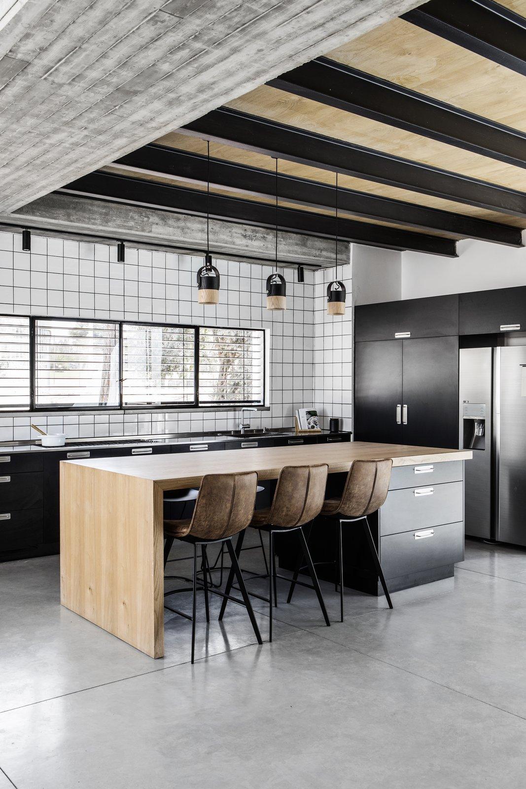 Kitchen, Refrigerator, Cooktops, Metal Counter, Colorful Cabinet, Concrete Floor, Ceramic Tile Backsplashe, Ceiling Lighting, and Pendant Lighting  Nir Am House by Shir Shtaigman