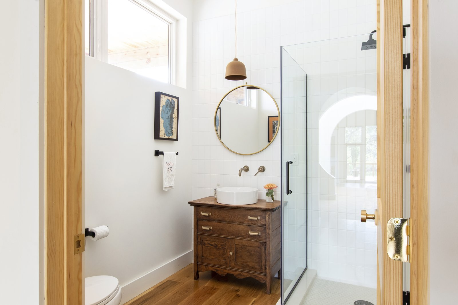 Bath Room, One Piece Toilet, Light Hardwood Floor, Vessel Sink, Corner Shower, Pendant Lighting, Subway Tile Wall, and Wood Counter  Westwood House