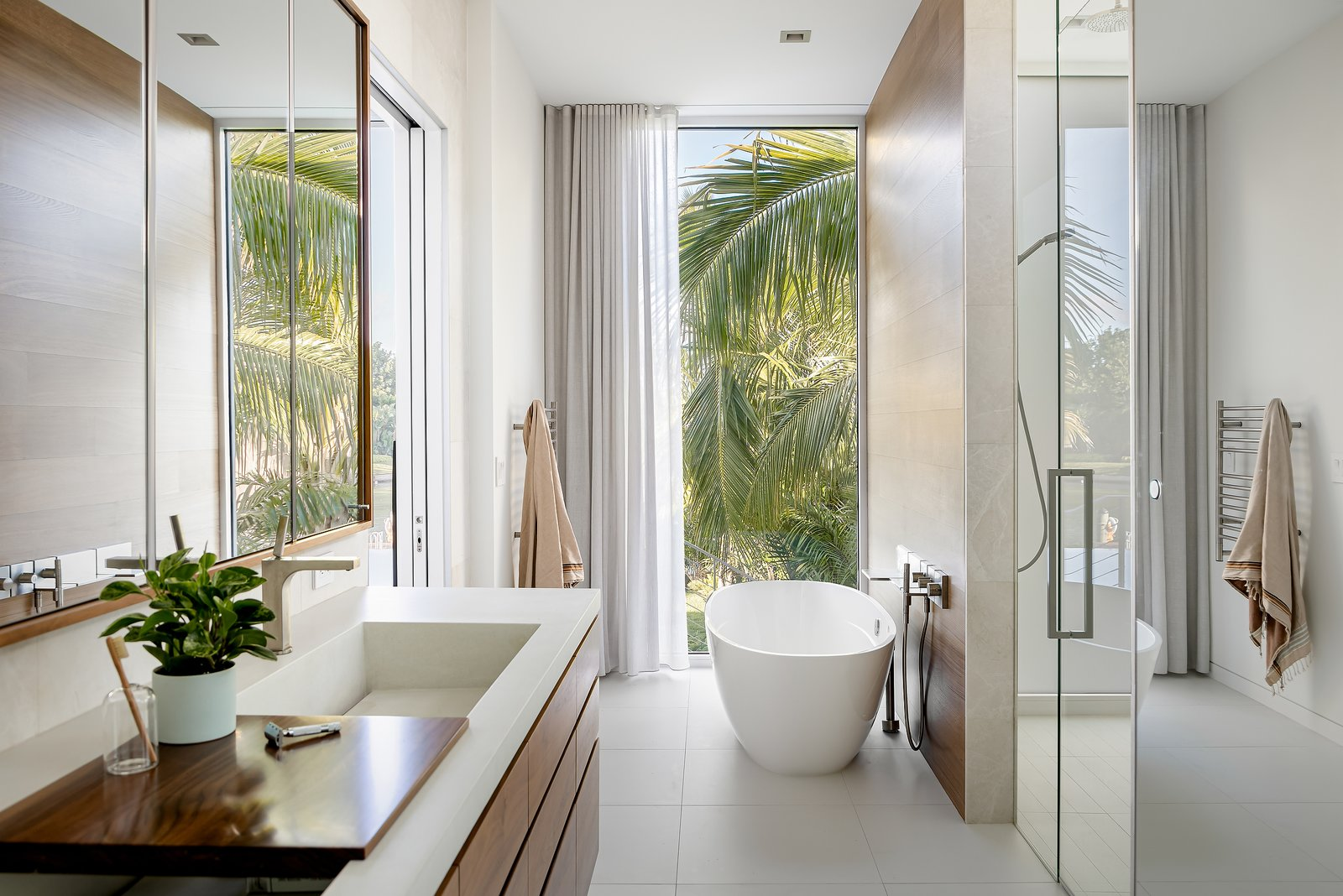 Bath Room, Stone Slab Wall, Concrete Counter, Porcelain Tile Floor, Freestanding Tub, Ceiling Lighting, Recessed Lighting, Soaking Tub, Wall Mount Sink, One Piece Toilet, and Enclosed Shower  Bayview House by Leader Design Studio